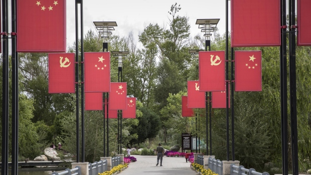 The Chinese national flag and the Chinese Communist Party flag hang on display at a park commemorating General Mu Shengzhong, also known as the father of the Qinghai-Tibet Highway, in Golmud, Qinghai province, China, on Sunday, July 22, 2018. Amid rising fears about a trade war, China's policy makers have unveiled measures to boost infrastructure construction and credit to smaller firms, as well as tax cuts.