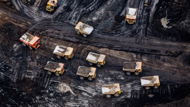 Heavy haulers are seen at the Suncor Energy Inc. Fort Hills mine in this aerial photograph taken above the Athabasca oil sands near Fort McMurray, Alberta, Canada, on Monday, Sept. 10, 2018. While the upfront spending on a mine tends to be costlier than developing more common oil-sands wells, their decades-long lifespans can make them lucrative in the future for companies willing to wait.