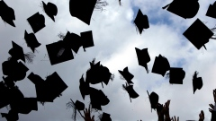 Students throw their mortarboards in the air during their graduation photograph at the University of Birmingham degree congregations on July 14, 2009
