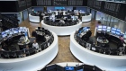 Traders monitor financial data as the DAX index curve shows stock information inside the Frankfurt Stock Exchange, operated by Deutsche Boerse AG, in Frankfurt, Germany.