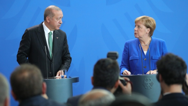 Recep Tayyip Erdogan, Turkey's president, left, and Angela Merkel, Germany's chancellor, stand at podiums during a news conference at the Chancellery in Berlin, Germany, on Friday, Sept. 28, 2018. Merkel is letting Turkey's leader in from the cold, a year after he accused Germans of using Nazi methods. Photographer: Krisztian Bocsi/Bloomberg
