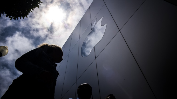 Pedestrians walk past an Apple Inc. store in San Francisco California U.S. on Thursday