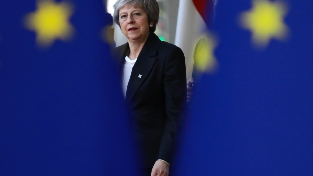 Britain's Prime Minister Theresa May is seen behind EU flags as she arrives at the European Council.