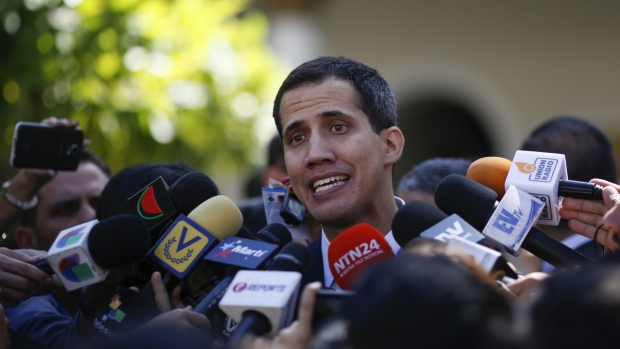 Juan Guaido, president of the National Assembly, talks to members of the media following a swearing in ceremony at the Federal Legislative Palace in Caracas, Venezuela, on Saturday, Jan. 5, 2019. A group of 12 Latin American nations plus Canada urged Venezuela's leader to hand power to the opposition-controlled National Assembly and call new elections, stepping up pressure on Nicolas Maduro days before he's due to start a new term. Photographer: Marco Bello/Bloomberg