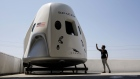 A person takes pictures of a mock up of the Crew Dragon spacecraft at SpaceX headquarters in Hawthorne, California.