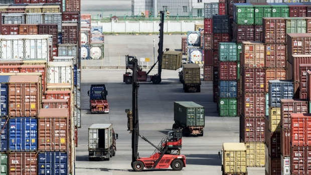 Trucks and forklifts operate as containers sit stacked at the Yangshan Deep Water Port in Shanghai, China, on Tuesday, July 10, 2018. China told companies to boost imports of goods from soybeans to seafood and automobiles from countries other than the U.S. after trade tensions between the world's two biggest economies escalated into a tariff war last week.