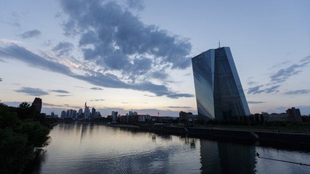The European Central Bank (ECB) skyscraper headquarters stand beside the River Main at dusk in Frankfurt, Germany.
