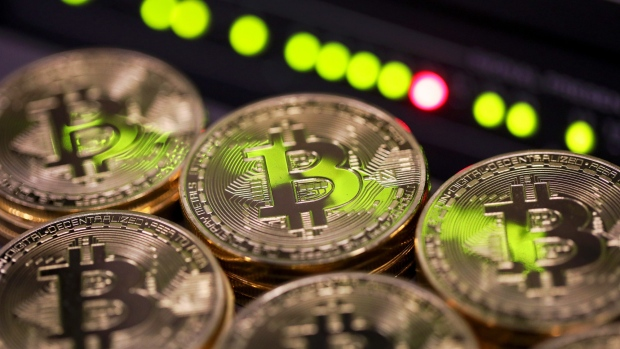 Stacks of bitcoins sit near green lights on a data cable terminal inside a communications room at an office in this arranged photograph in London, U.K.,