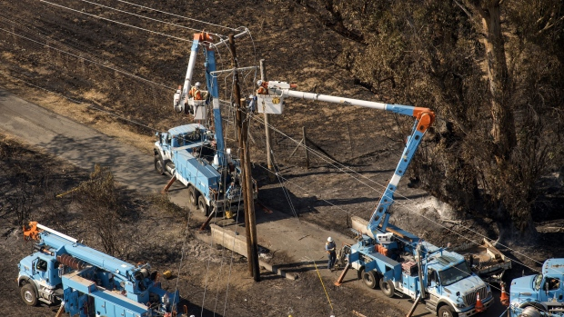 Pacific Gas & Electric Co. (PG&E) employees work to fix downed power lines burned by wildfires in this aerial photograph taken above Santa Rosa, California, U.S., on Thursday, Oct. 12, 2017.