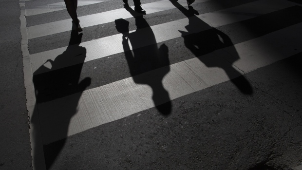 The shadow of pedestrians are seen on the ground of a crosswalk in Toronto, Ontario, Canada.