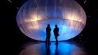 Visitors stand next to a high altitude WiFi internet hub, a Google Project Loon balloon, on display at the Airforce Museum in Christchurch on June 16, 2013.