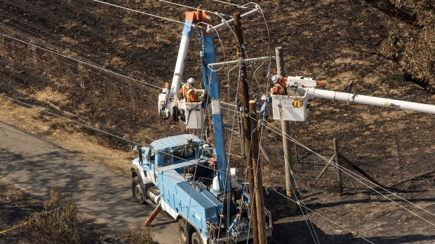 Pacific Gas & Electric Co. (PG&E) employees work to fix downed power lines burned by wildfires in this aerial photograph taken above Santa Rosa, California, U.S.