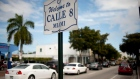 Cars pass by a sign welcoming people to Calle 8, or Eighth Street, Miami