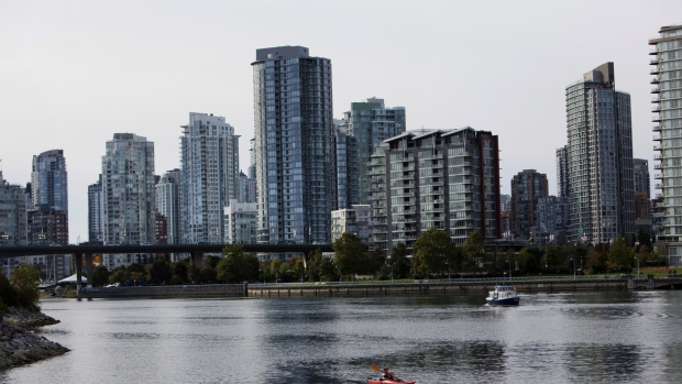 The city skyline stands as a woman kayaks at False Creek in downtown Vancouver, British Columbia, Canada, on Thursday, Oct. 3, 2013.