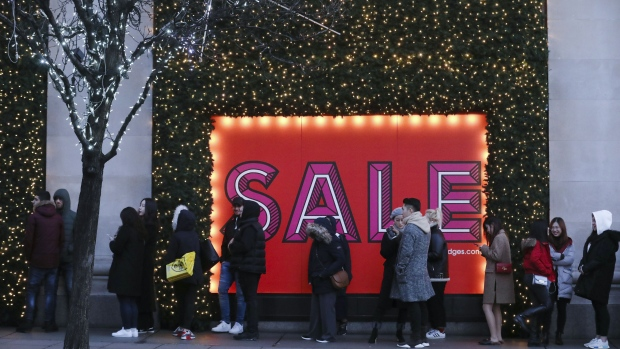 Shoppers stand in line next to a large sale sign for the Boxing Day holiday sales at the Selfridges Ltd. department store in central London, U.K., on Tuesday, Dec. 26, 2017. U.K. annual growth in the third quarter slowed to 1.7 percent, slightly higher than previously estimated but still the weakest pace in 4 1/2 years, the Office for National Statistics said on Friday. Photographer: Luke MacGregor/Bloomberg
