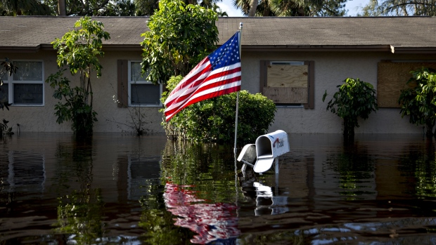 A U.S. flag flies outside a flooded home in Bonita Springs, Florida, U.S., on Tuesday, Sept. 12, 2017. Hurricane Irma smashed into Southern Florida as a Category 4 storm, driving a wall of water and violent winds ashore and marking the first time since 1964 the U.S. was hit by back-to-back major hurricanes.
