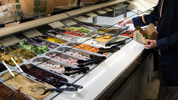 "A man serves himself from the ""Build Your Own Salad"" bar at a Whole Foods Market Inc. location in New York."