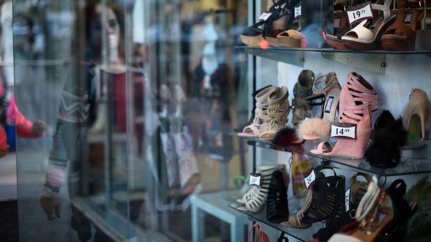 The reflection of a shopper is seen on a window as shoes are displayed for sale on Steinway Street in the Queens borough of New York, U.S.