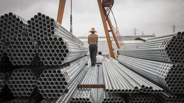 Workers prepare to lift bundles of steel pipe with a crane at a stockyard on the outskirts of Shanghai, China. Photgrapher: Qilai Shen/Bloomberg