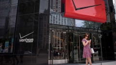 A pedestrian uses a smartphone outside a Verizon Communications Inc. store in downtown Chicago, Illinois, U.S.