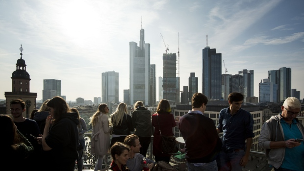 Guests stand at the rooftop of a shopping mall and look at the skyline and Frankfurt's financial district. Skyrocketing costs for housing have become a major issue in cities across Germany, with local government scrambling to find policy solutions. Photographer: Thomas Lohnes/Getty Images Europe