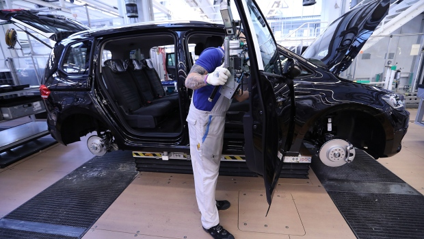 A worker fits a door to a Volkswagen Touran Sport Utility Vehicle (SUV) on the assembly line at the Volkswagen AG (VW) factory in Wolfsburg, Germany, on Tuesday, Oct. 30, 2018. VW has managed one of the more confident outlooks in an otherwise gloomy reporting season for carmakers and suppliers.