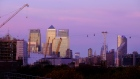 Skyscrapers in the Canary Wharf business, financial and shopping district, including One Canada Square, second left, stand on the skyline above residential buildings in London, U.K., on Wednesday, Nov. 14, 2018. The City of London averted one disaster with the draft Brexit deal announced Wednesday, but the bottom line is that banks, brokers and asset managers will continue to prepare for the talks going off the rails.
