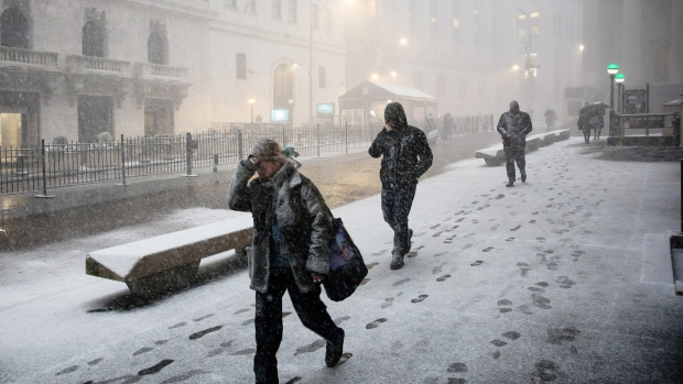 Pedestrians walk down Broad Street in the snow in front of the New York Stock Exchange (NYSE) in New York, U.S., on Wednesday, Jan. 30, 2019.