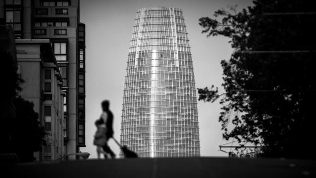 (EDITORS NOTE: Image has been converted to black and white.) Pedestrians cross the street as the Salesforce Tower stands in San Francisco, California, U.S., on Thursday, May 10, 2018. The building, the tallest office tower west of the Mississippi river, opened with a ceremony crowded with local officials on Tuesday, representing the indelible mark San Francisco's largest private employer has made on the city.