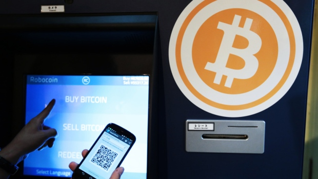 Eugene Aono, a spokesperson for BMEX bitcoin exchange, demonstrates usage of the company's Robocoin-branded automated teller machine (ATM) at The Pink Cow restaurant and bar in Tokyo, Japan, on Wednesday, June 18, 2014.