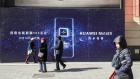 Pedestrians walk past an advertisement for the Huawei Technologies Co. Mate 20 smartphone in Beijing