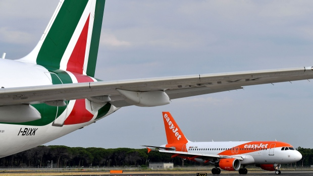 An EasyJet airplane rolls on the tarmac past an Alitalia plane on June 21, 2018 at the Fiumicino Airport, in Rome.