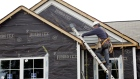 A worker installs vinyl siding on a Centex home under construction at the Pointe in Clayton, North Carolina, U.S.