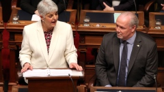 Premier John Horgan looks on as Finance Minister Carole James delivers the budget speech