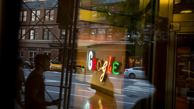 Pedestrians are reflected in a window looking into a lobby of the Google Inc. offices in New York, U.S., on Tuesday, Aug. 22, 2016.