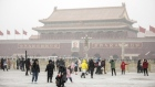 People pose for photographs at Tiananmen Square as snow falls in Beijing, China