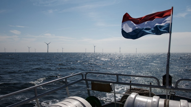 The national flag of the Netherlands flies from the stern of a boat as wind turbines stand beyond at the Egmond aan Zee wind farm operated by Noun Energy NV, a unit of Vattenfall AB, in the North Sea off the coast of Ijmuiden, Netherlands, on Thursday, July 3, 2014. The Dutch government is banking on offshore wind to help meet its target of sourcing 14 percent of the country's energy from renewables by the end of the decade, and cutting carbon dioxide emissions by as much as 95 percent by 2050.