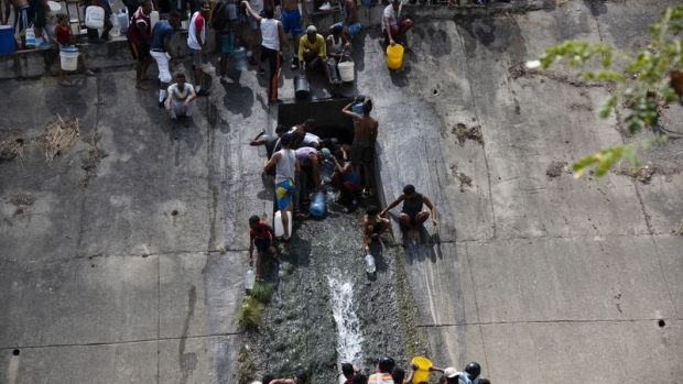 Residents of San Agustin taking water from pipe in the Guaire river west of Caracas on March 11. Click here for an explanation of what's behind the crisis in Venezuela and here for more of Bloomberg's most compelling political photos from the past week.  Photographer: Carlos Becerra/Bloomberg