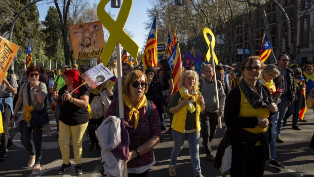 Protesters carry Catalan Independence flags and yellow ribbons during a demonstration titled 'Self-determination is not a crime' on March 16, 2019 in Madrid.
