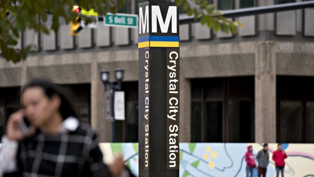 A pedestrian walks past a sign for the Crystal City Metro station in Arlington, Virginia.