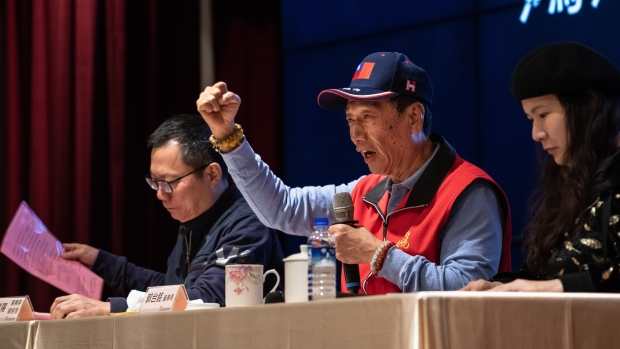 Terry Gou, chairman of Foxconn Technology Group, center, gestures while speaking as Calvin Chih, chief executive officer of FIH Mobile Ltd., a subsidiary of Foxconn, left, looks on during a news conference at Foxconn's headquarters in New Taipei, Taiwan, on Tuesday, March 12, 2019. Billionaire Gou responded with outrage to a low-key Microsoft Corp. patent lawsuit, accusing the software giant of a personal attack against him and his company.