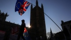 Anti-Brexit campaigners wave a European Union flag and a Union Jack, also known as a Union Flag, during a protest near the Houses of Parliament in London, U.K.,