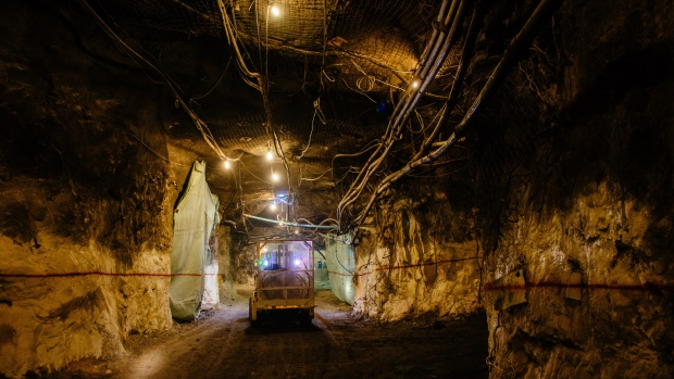 Lights illuminate a mining truck moving through an underground tunnel at a gold mine.