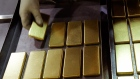 An employee arranges one kilogram gold bars at the Perth Mint Refinery, operated by Gold Corp., in Perth, Australia, on Thursday, Aug. 9, 2018.
