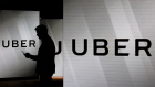 A man checks his smartphone whilst standing amongst illuminated screens bearing the Uber Technologies Inc. logo in this arranged photograph in London, U.K., on Tuesday, June 26, 2018.