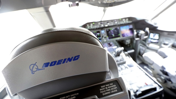 A logo sits on a pilot's seat in the cockpit of a Boeing Co. 787 Dreamliner