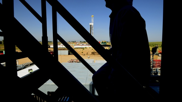 The silhouette of a contractor is seen walking up stairs at an Anadarko Petroleum Corp. oil rig site in Fort Lupton, Colorado.