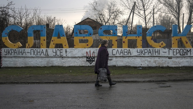 A woman passes in front of the Slaviansk sign that is full of holes that were caused by the clashes between the Ukrainian government and rebel groups during the battle between the Ukrainian government and rebel groups during a journey through different cities of Ukraine on April 3, 2019 in Slaviansk, Ukraine.