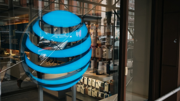 The AT&T Inc. logo is displayed outside a store in New York, U.S., on Wednesday, June 13, 2018. AT&T Inc.'s sweeping court victory allowing its takeover of Time Warner Inc. delivers a sharp setback to the Justice Department's new approach to policing mergers under President Donald Trump and promises to spark a merger wave across industries.