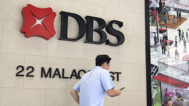 A man walks past a DBS Group Holdings Ltd. logo displayed outside of the company's branch in the central business district (CBD) of Singapore, on Monday, Feb. 12, 2018. DBS Group Holdings Ltd. rose the most in almost eight years in Singapore trading after Southeast Asia's biggest lender posted fourth-quarter profit growth and promised higher dividends.